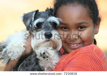 Little girl and her miniature schnauzer puppy. - stock photo