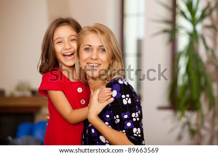 little girl and her mother holding and laughing, family moment - stock photo