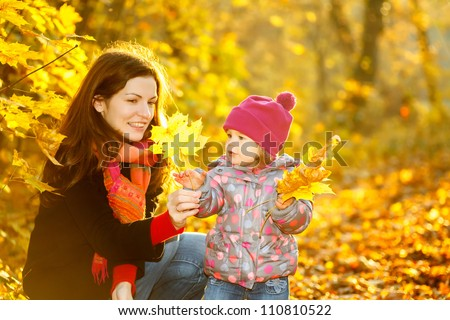 Little girl and her mother in the autumn park