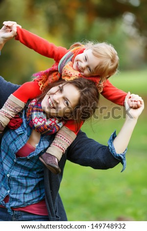 Little girl and her mother in the autumn park - stock photo
