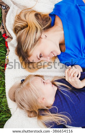 Little girl and her mother lying together on grass in summer. Family picnic. Beautiful young mom and her cute daughter blonds in blue dresses hold hands and look at each other. Overhead top view - stock photo