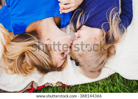 Little girl and her mother lying together on grass in summer. Family picnic. Beautiful young mom kiss cute daughter in head, both blonde in blue dresses and holding hands. Overhead top view - stock photo