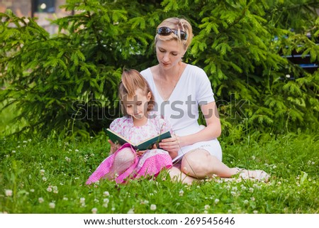 Little girl and her mother reading a book while they sitting and enjoy in beautiful nature - stock photo
