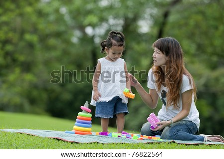 Little girl and her mother were playing toys in the garden. - stock photo