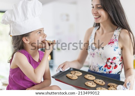 little girl and her mother with a tray of freshly baked cookies - stock photo
