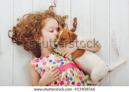 Little girl and her puppy whispers on wood background. - stock photo