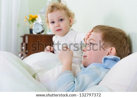 Little girl and her sick brother lying in bed at home - stock photo
