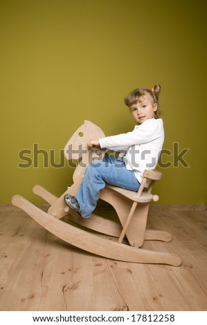 Little girl and horse - rocking chair - stock photo