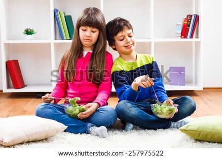 Little girl and little boy don't want to eat vegetables.We don`t like vegetables! - stock photo