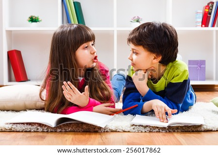 Little girl and little boy have decided to take a break from homework and now they are having conversation.Children talking - stock photo
