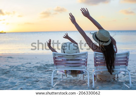 Little girl and mother sitting on beach chairs at sunset - stock photo