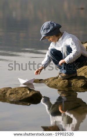 Little girl and paper boat - stock photo