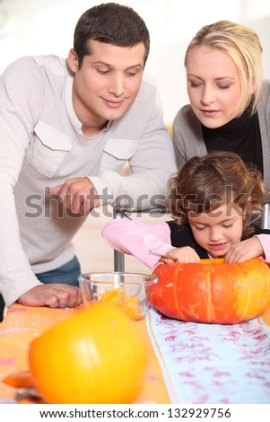 Little girl and parents carving pumpkin for Halloween - stock photo