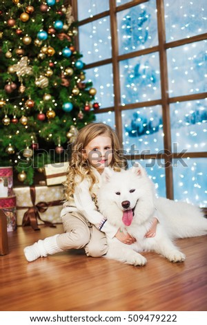 Little girl and samoyed dog near the window