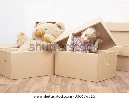 little girl and teddy bear in box, family in move