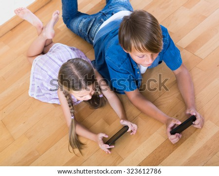Little girl and teenage russian boy burying in mobile phones  - stock photo