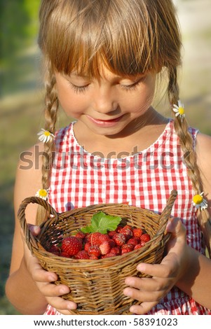 Little girl and the basket of wild strawberries - stock photo
