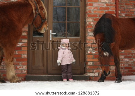 Little girl and two horses standing near the cottage door in winter - stock photo