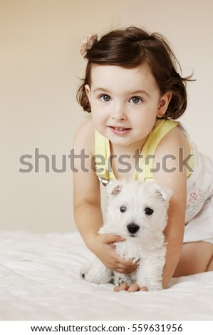 Little girl and westie puppy
