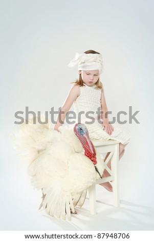 Little girl and white turkey. Studio shot - stock photo