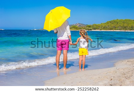 Little girl and young dad at white beach with yellow umbrella - stock photo