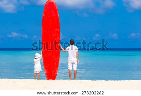 Little girl and young dad with surfboard during summer vacation - stock photo