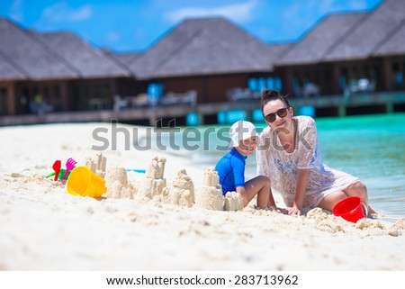 Little girl and young mom playing with beach toys on tropical vacation - stock photo