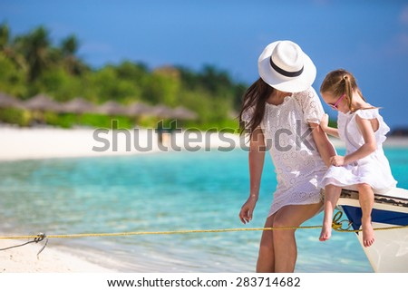 Little girl and young mother on boat during beach vacation
