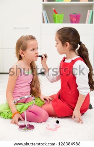 Little girl applying lipstick on her girlfriend's mouth - stock photo