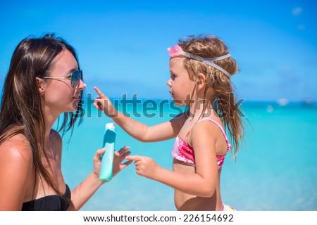 Little girl applying sunblock cream on her mom nose - stock photo