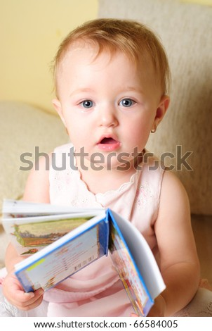 Little girl are readign the book, sitting on the sofa