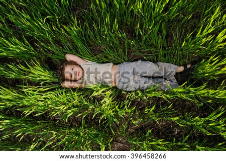 Little girl are resting on the green grass in summer. Happy child, kid lying on grass on picnic on the nature. Funny kids relax, play outdoors in park. Top view. - stock photo