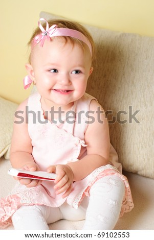 Little girl are sitting on the sofa and playing with mobile phone