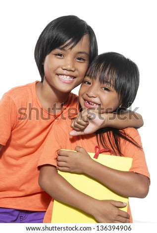 little girl Asian sisters arms around holding a books - stock photo