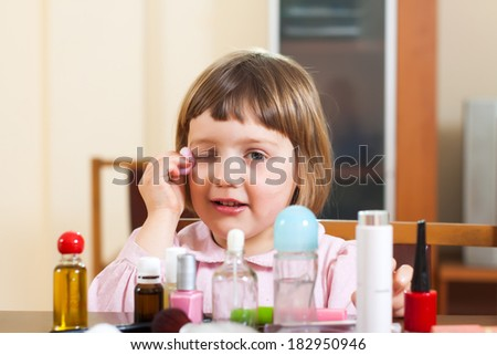 little girl at  table with cosmetic products - stock photo