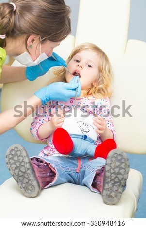 Little girl at the dentist sitting patiently in the chair.