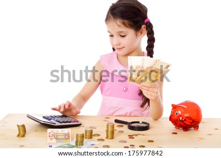 Little girl at the table counts money, isolated on white - stock photo