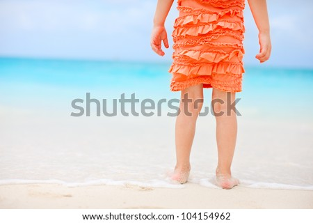 Little girl at tropical beach close up on legs