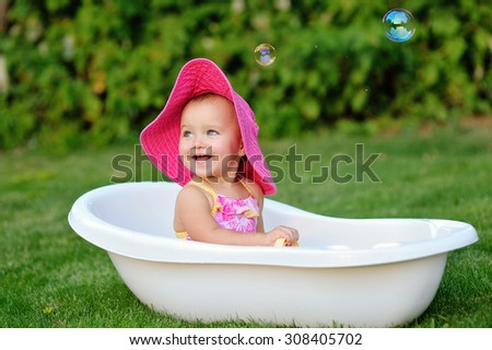 little girl bathes in a bath with soap bubbles. - stock photo