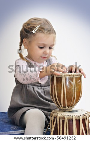 Little girl beats the drum. Shallow depth with focus on drum