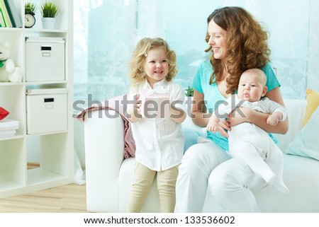 Little girl being happy with her present, her mom holding a newborn - stock photo