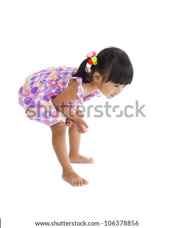 little girl bending over to have a closer look at something - stock photo