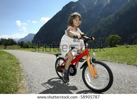 little girl biking in the mountains - stock photo