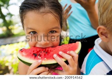 Little girl biting a piece of fresh watermelon - stock photo