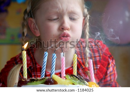 Little girl blowing birthday candles - stock photo
