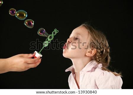 Little girl blowing bubbles. Studio shot on black - stock photo