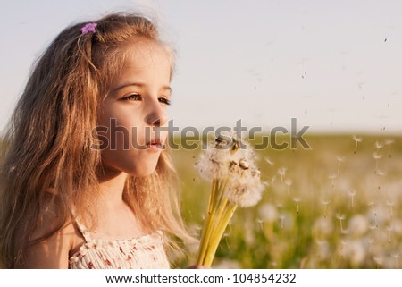 little girl blowing dandelions - stock photo