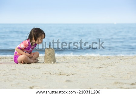 Little girl blowing on cake made with sand. Photo taken near the ocean. - stock photo