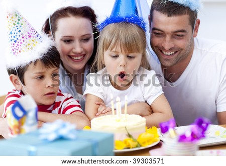 Little girl blowing out candles in her birthday with her family