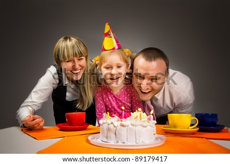 Little girl blowing out candles in her birthday with her happy family - stock photo